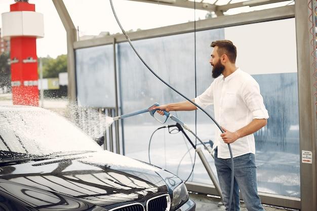 Mens die zijn auto in een wasstation wast