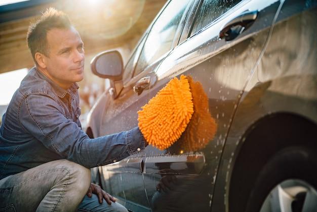 Mens die zijn auto met washandschoen wast
