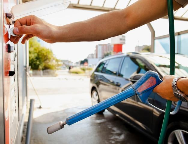 Mens die zijn auto voorbereidingen treft te wassen