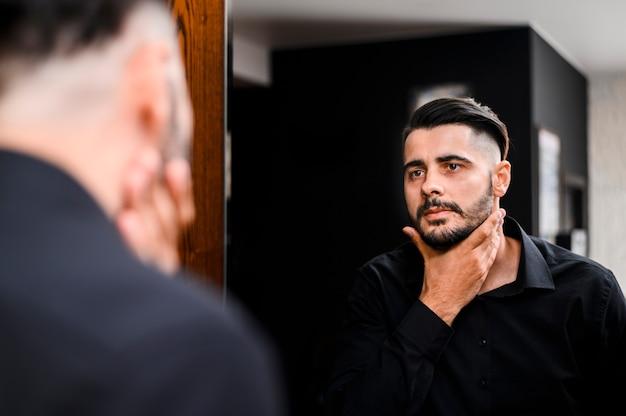 Mens die zijn baard in de spiegel controleert