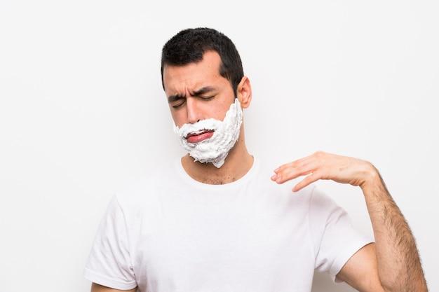 Mens die zijn baard met vermoeide en zieke uitdrukking scheert