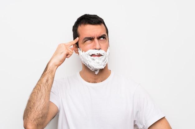 Mens die zijn baard over geïsoleerd wit scheert dat twijfels en het denken heeft