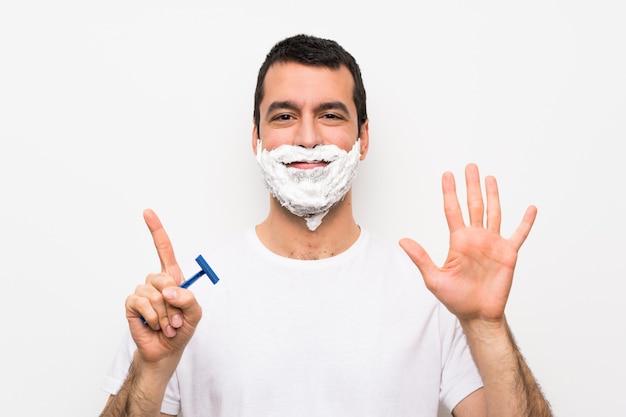 Mens die zijn baard over geïsoleerd wit scheert dat zes met vingers telt