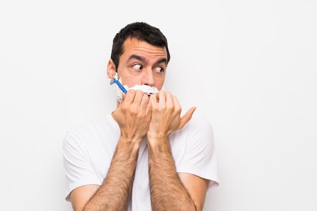 Mens die zijn baard over geïsoleerde witte achtergrond scheert zenuwachtig en bang die handen aan mond zetten