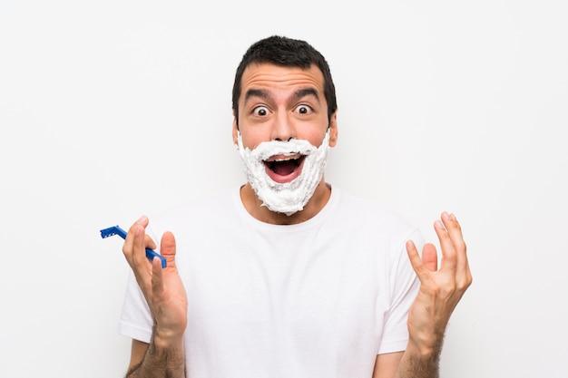 Mens die zijn baard over geïsoleerde witte muur met geschokte gelaatsuitdrukking scheert