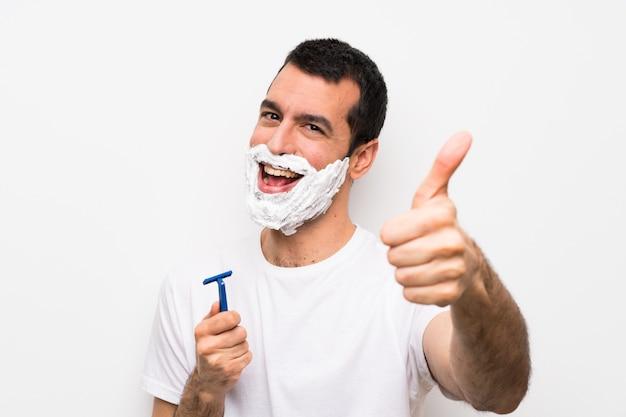 Mens die zijn baard over geïsoleerde witte muur met omhoog duimen scheert omdat er iets goeds is gebeurd