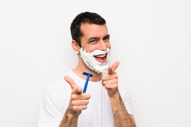 Mens die zijn baard over geïsoleerde witte muur scheert die aan de voorzijde en het glimlachen richt