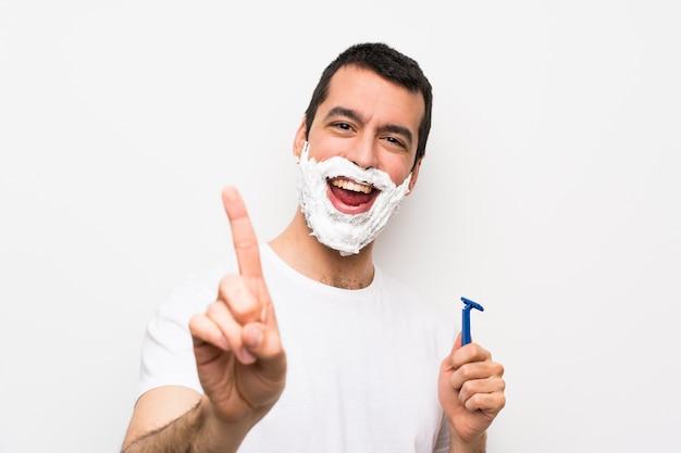 Mens die zijn baard over geïsoleerde witte muur scheert die een vinger toont en opheft