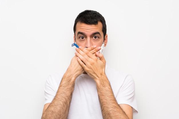 Mens die zijn baard over geïsoleerde witte muur scheert die mond behandelt met handen