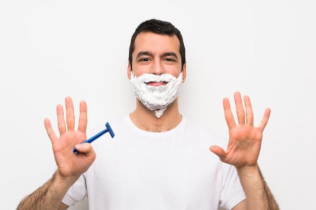 Mens die zijn baard over geïsoleerde witte muur scheert die negen met vingers telt