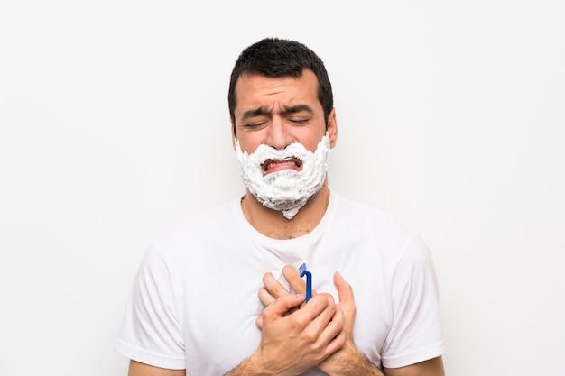 Mens die zijn baard over geïsoleerde witte muur scheert die pijn in het hart heeft
