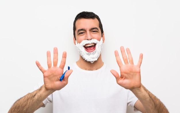 Mens die zijn baard over geïsoleerde witte muur scheert die tien met vingers telt