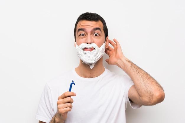 Mens die zijn baard over geïsoleerde witte muur scheert die twijfels heeft