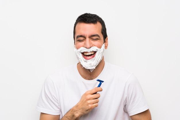 Mens die zijn baard over geïsoleerde witte muur scheert die veel glimlacht