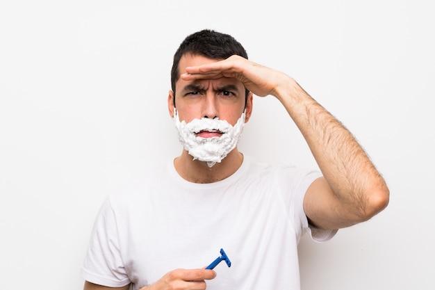 Mens die zijn baard over geïsoleerde witte muur scheert die ver weg met hand kijkt om iets te kijken