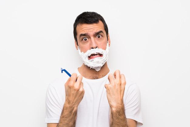 Mens die zijn baard scheert over geïsoleerde witte muur gefrustreerd door een slechte situatie