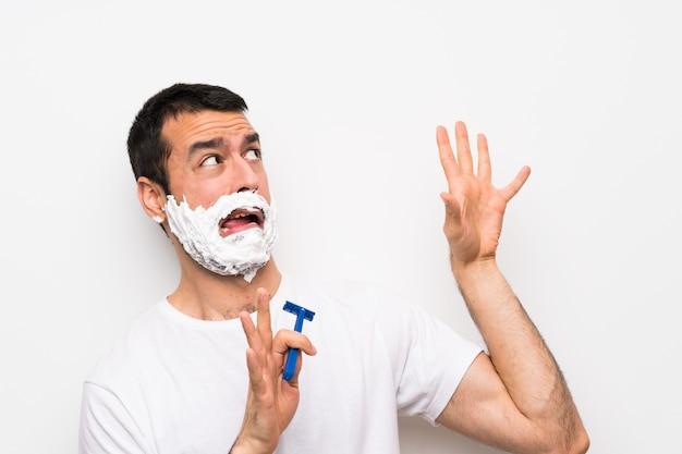 Mens die zijn baard scheert over geïsoleerde witte zenuwachtig en bange muur