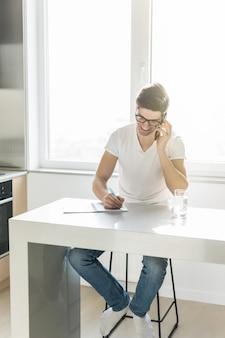 Mens die zijn celtelefoon met behulp van terwijl het werken aan financiën in zijn huiskeuken.