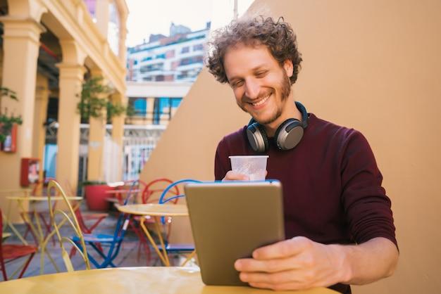 Mens die zijn digitale tablet gebruiken terwijl het drinken van bier.