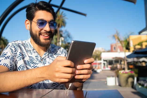 Mens die zijn digitale tablet in openlucht gebruiken.