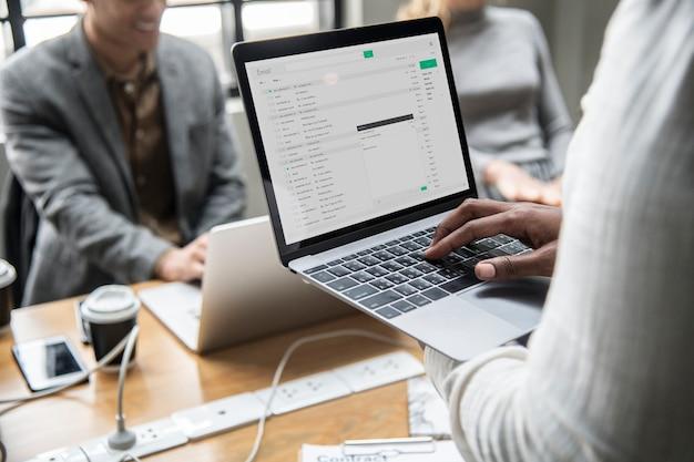 Mens die zijn e-mail op laptop controleert