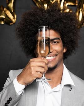 Mens die zijn gezicht behandelt met een glas champagne