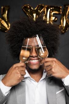 Mens die zijn gezicht behandelt met glazen en glimlachen