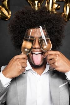 Mens die zijn gezicht behandelt met glazen en zijn tong uit steekt