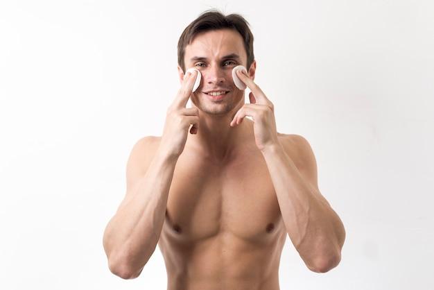 Mens die zijn gezicht met katoenen schijven schoonmaakt