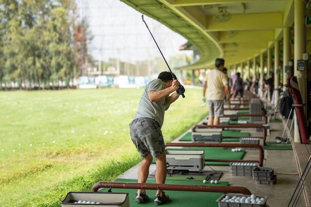 Mens die zijn golfschommeling uitoefent bij golf driving range.