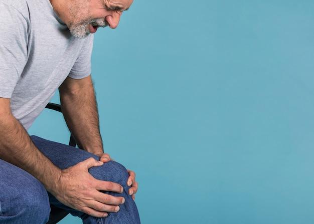 Mens die zijn knie in pijn houden terwijl het zitten op stoel tegen blauwe achtergrond