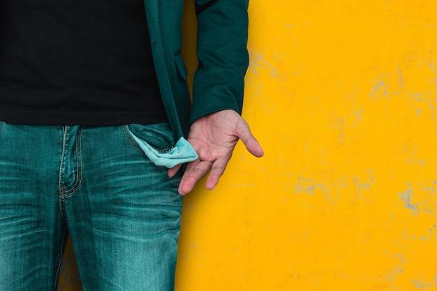 Mens die zijn lege zak op gele muur toont