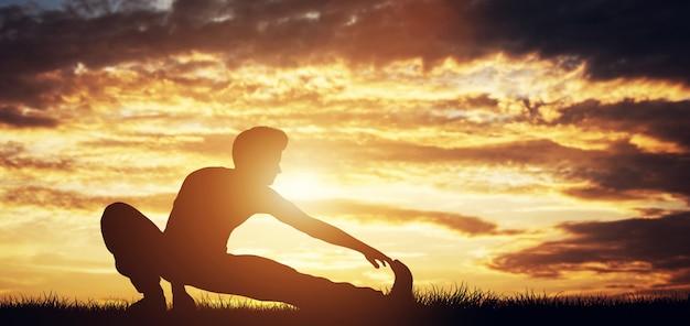 Mens die zijn lichaam in de zonsondergang uitrekt.