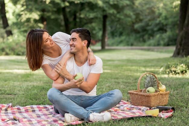 Mens die zijn meisje bekijkt terwijl het houden van een appel