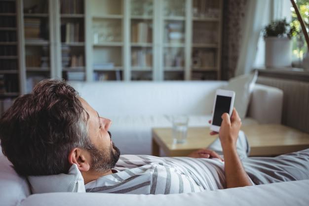 Mens die zijn mobiele telefoon in woonkamer met behulp van