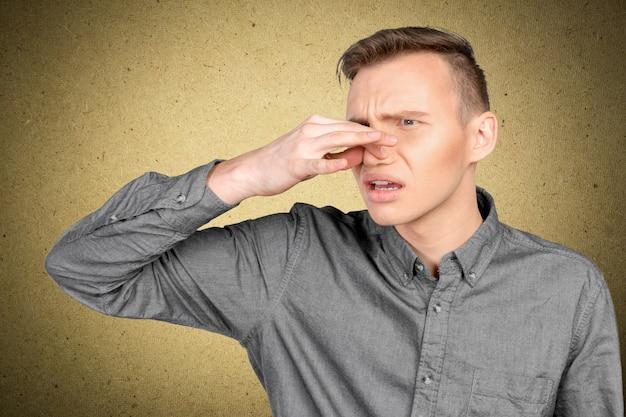 Mens die zijn neus houdt tegen een stank