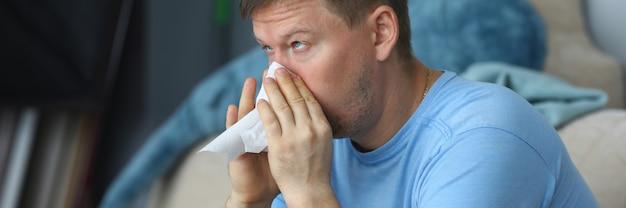 Mens die zijn neus in een servet blaast terwijl het zitten