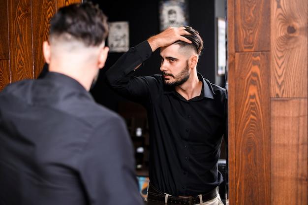 Mens die zijn nieuw kapsel in een spiegel controleert