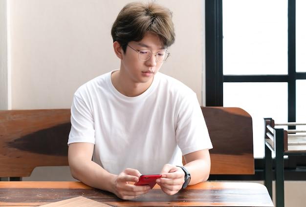 Mens die zijn oogglazen draagt die de aziatische mens van smartphone wat betreft smartphone gebruiken.