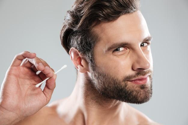 Mens die zijn oren met oorstok schoonmaken