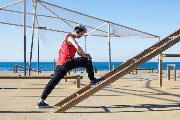 Mens die zijn spieren uitrekt alvorens buitensporten te beginnen uit te oefenen
