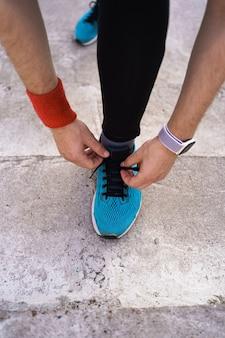 Mens die zijn sportschoenen op concrete achtergrond bindt