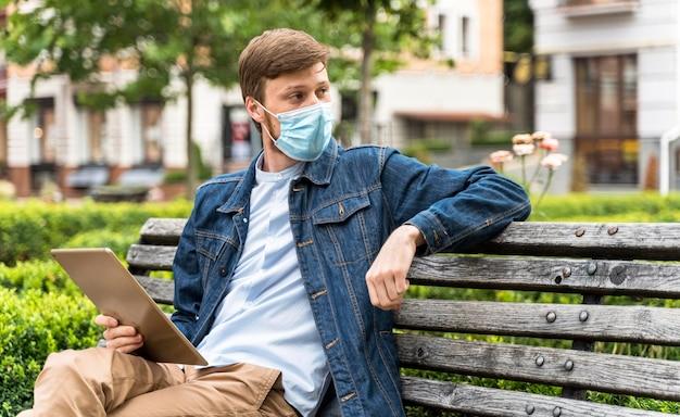 Mens die zijn tablet controleert terwijl hij een medisch masker met exemplaarruimte draagt