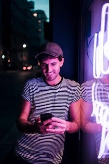 Mens die zijn telefoon en glimlach bekijkt