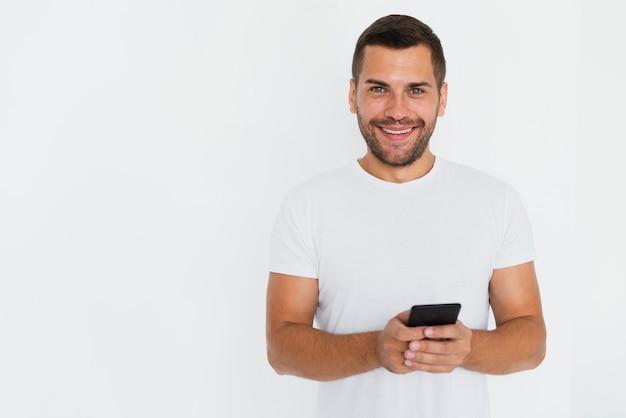 Mens die zijn telefoon op handen en witte achtergrond heeft
