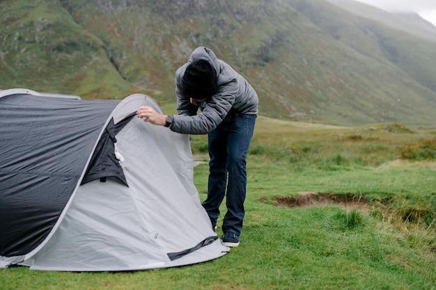 Mens die zijn tent opslaat terwijl het regent