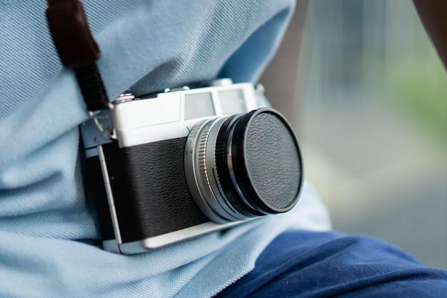 Mens die zijn uitstekende camera van de filmafstandsmeter dicht omhoog hangt. concept van retro- en vintage fotografie.
