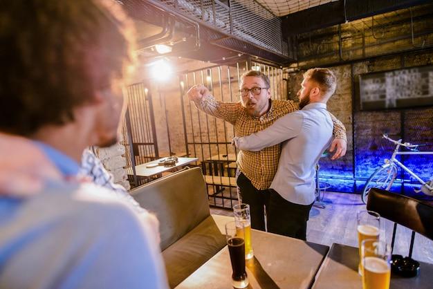 Mens die zijn vriend tegenhoudt om in een bargevecht te komen. groep man drinken in een bar en vechten.