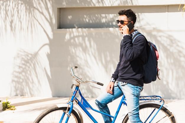 Mens die zonnebril draagt die op blauwe fiets zitten die over zijn mobiele telefoon spreekt