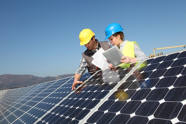Mens die zonnepanelentechnologie toont aan studentenmeisje
